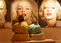 Two women looking at pictures of Marilyn Monroe