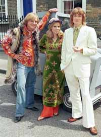 Two hippies dressed in bright clothing and a man in a white suit