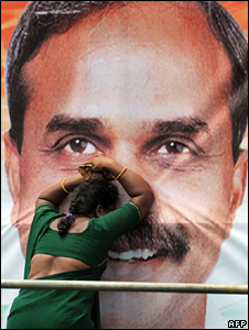 A woman grieving in front of a poster of YSR Reddy
