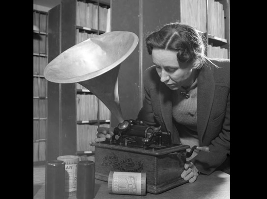 Assistant librarian Aline Carter listens to a wax cylinder recording on an Edison phonograph.