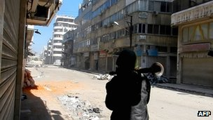 A man carries a Rocket Propelled Grenade (RPG) in the al-Hamidiya neighbourhood of Homs