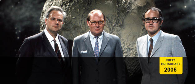 Patrick Moore, Cliff Michelmore and James Burke, standing in front of a large model of the moon