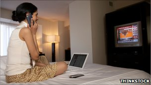 Woman on bed with phone, laptop and television