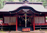 Red-painted shrine at Yatsuki Tsutsukowake decorated with paper streamers and rainbow ribbons