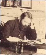 Silvanus Trevail sitting at a desk