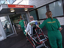 Paramedics pushing patient on trolley into hospital