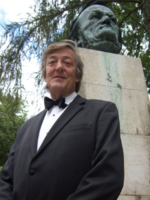 Stephen Fry in a tuxedo stands by a bust of Richard Wagner