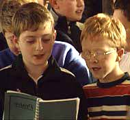 Boys singing from a hymn book