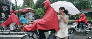 A couple ride a moped in the rain