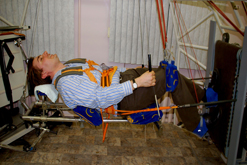 Richard Hollingham exercising simulating no gravity strapped into a contraption and lying horizontally.