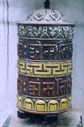 Prayer wheel, a carved and painted cylindrical drum standing upright on a central spindle