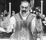 Padre Pio leading a service in priestly robes with coverings over the palms of his hands. Image credit: Padre Pio Devotions