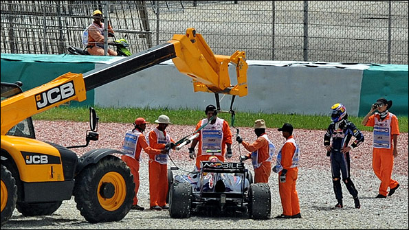 Mark Webber watches as his Red Bull is removed from a gravel trap after an engine failure in Friday practice at the Malaysian Grand Prix