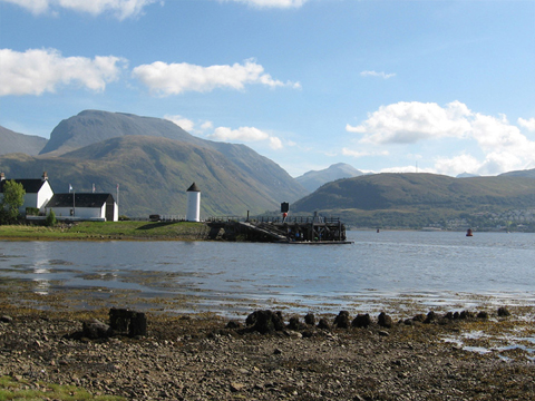 Colour view from a rocky beach across Loch Linnhe to Ben Nevis. In the middle distance is a quayside featuring a cylindrical tower, pitched-roofed buildings and a wooden pier with slipway.