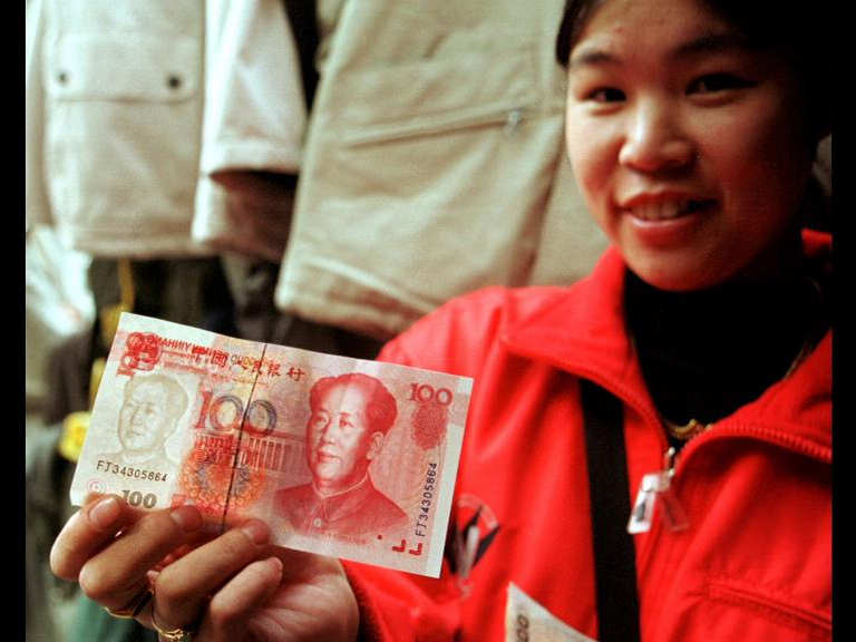 Photo of a woman holding up a 100 Yuan note