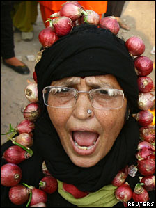 Indian woman wearing a garland made with onions during a protest against the price rise