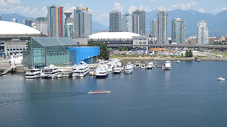 View of east-central Vancouver, with coastal range mountains in background, and two Olympic venues in middle. BC Place on the left will host the Opening and Closing ceremonies. GM Place (or Canada Hockey place) in the centre, will host the hockey events during the Vancouver 2010 Winter Olympics (officially known as the XXI Olympic Winter Games). copyright Arlene Gregorius/BBC
