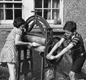 Two children putting washing though a mangle, 1941.