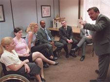 A still from the sitcom 'The Office'. David Brent welcomes new members of staff, including a lady who is a wheelchair user