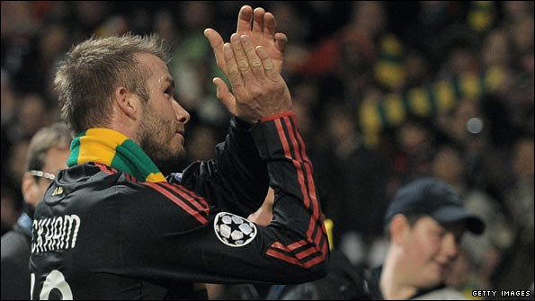 Beckham puts a green and gold scarf around his neck