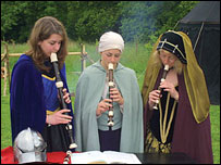 Three women playing recorders in period dress