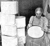 A photograph showing a Victorian woman working on making hat boxes