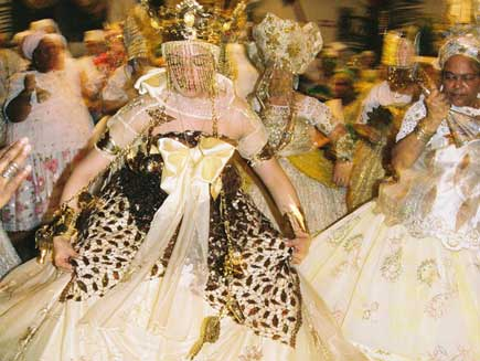 Woman in an elaborate dress wearing a gold plated crown, dancing.