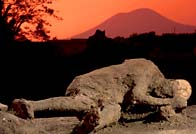 Photograph showing a sunset reddened sky around Vesuvius beyond the poignant cast of a Pompeian's body