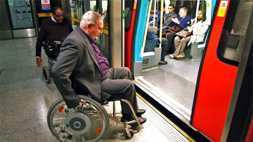 Two wheelchair users boarding a tube train