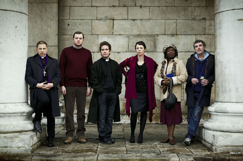 The cast of Rev outside the church, from left to right: Simon McBurney as the Archdeacon, Miles Jupp as lay reader Nigel, Tom Hollander as Reverend Adam Smallbone, Olivia Colman as Alex Smallbone, Ellen Thomas as Adoha, and Steve Evets as Colin