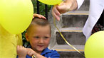 Child with balloon holding parent's hand