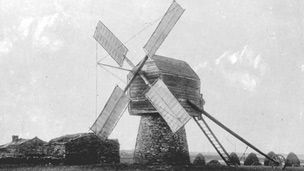 Four sailed timber and stone construction windmill with low stone buildings behind.