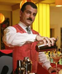 A man dressed in a smart uniform pouring a cocktail