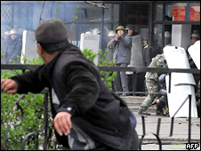 A Kyrgyz opposition supporter throws a projectile at riot police during an anti-government protest in Bishkek on 7 April 2010