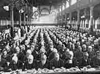 Newspaper picture showing a packed hall of workhouse staff sitting down to dinner