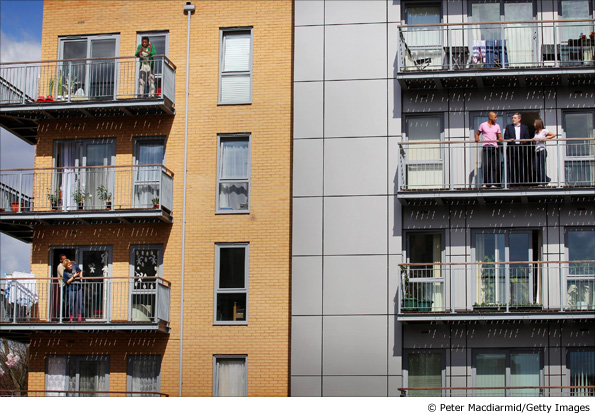 People look across as Gordon Brown as he talks to residents on the balcony of their newly built flat in London