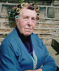 An elderly woman wearing hair rollers