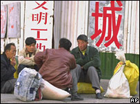 Migrant workers rest on a Beijing street on Sunday Febuary 27, 2000. China Daily newspaper reported that last year only 22 million out of the 70 million unemployed rural laborers who went to cities found work. Chinese leaders worried that frequent protest