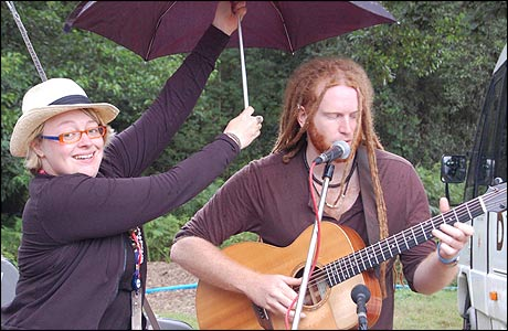 Linda Walker holds an umbrella over Newton Faulkner