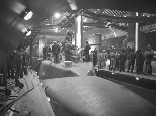 A film crew standing on the hull of a submarine, inside a huge metallic tanker.