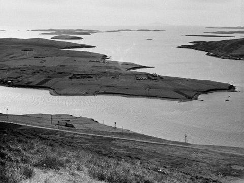 Black and white view looking down at the flat, grassy island of Trondra from the Hill of Easterhoull.