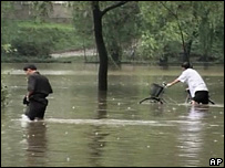 Two people wading through floods in North Korea