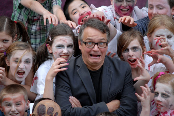 Charlie Higson surrounded by school children dressed as zombies.