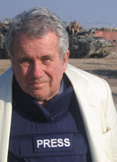 Presenter Martin Bell stands in front of a tank, wearing a bulletproof vest with the word PRESS on it