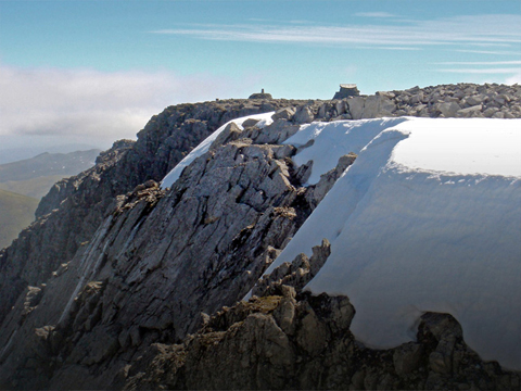 View across rocks, snow and ice to the flat summit of Ben Nevis.