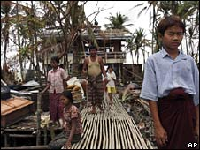 A family stand outside their damaged house in the Irrawaddy Delta on 11 May 2008