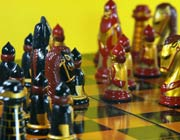 Chess pieces, decorated in red, gold and black, in the middle of a game