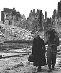British soldier and French civilian pick their way through what remains of Caen, July 1944