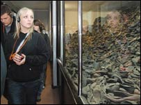 Student next to a display case full of Holocaust victims' shoes