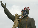 US Marine covering the face of the statue of Saddam Hussein with the US flag in al-Fardous square.